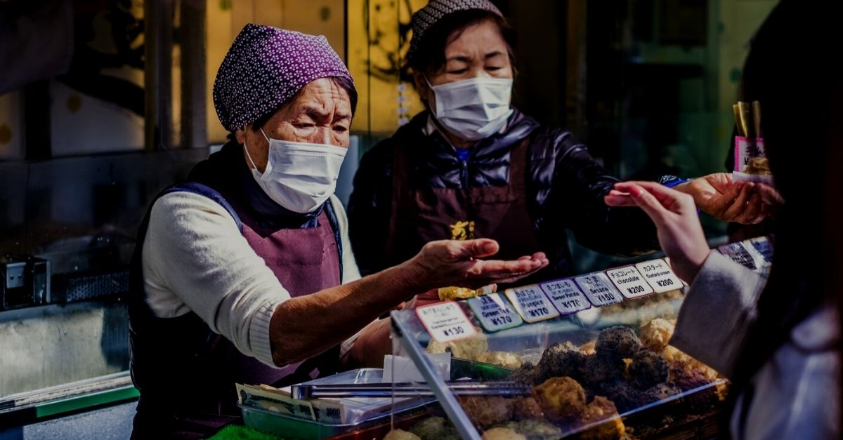 Asian workers in market selling food