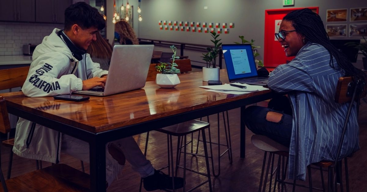 people at their laptops in coffee shop with their startup