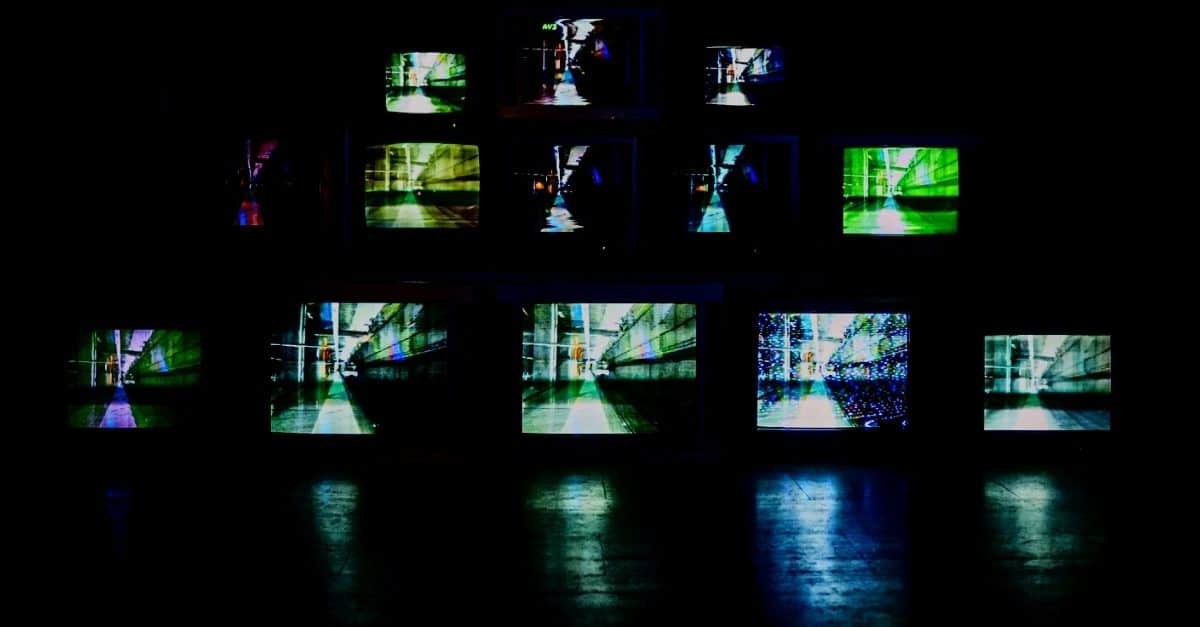 Photo by Murai .hr on Unsplash. Image of TV screens in dark room